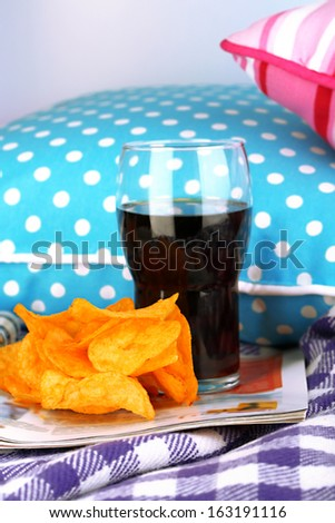 Chips in bowl, cola and TV remote on plaid on pillows background - stock photo