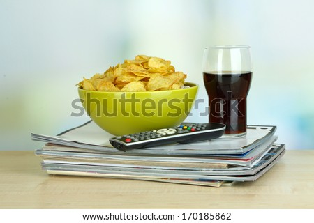 Chips in bowl, cola and TV remote on wooden table on room background - stock photo