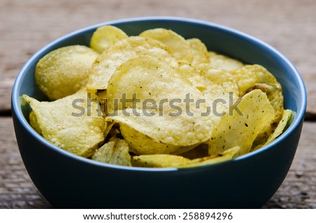 chips with herbs in a blue ceramic bowl on a wooden table - stock photo