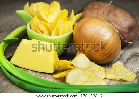 Chips with onion, cheese and potato on wooden boards  - stock photo