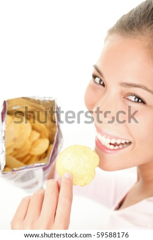 Chips. Woman eating bag of chips / crisps - smiling happy looking at camera. Beautiful young Caucasian / Asian emale model. - stock photo