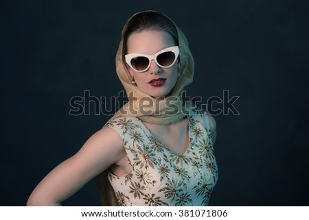 Chique vintage 50s fashion woman wearing sunglasses and scarf around head. - stock photo