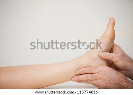 Chiropodist examining the foot of a patient in a medical room