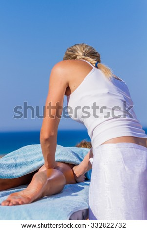 chiropractic massage therapy woman at sea resort - stock photo