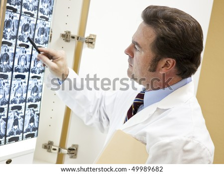 Chiropractor examines a CT scan of a patient's spine. - stock photo