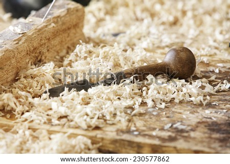 chisel on a wooden board with sawdust shavings. - stock photo