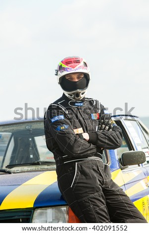 CHISINAU, MOLDOVA - APRIL 2, 2016: Drivers face in helmet before race. Auto pilot in front of his sport car. Auto slalom competition.in Chisinau, Moldova on April 2, 2016