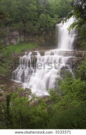 Chittenango Falls in central New York state. This beautiful waterfall tumbles across many rock ledges creating a beautiful scene and an almost tropical setting. - stock photo