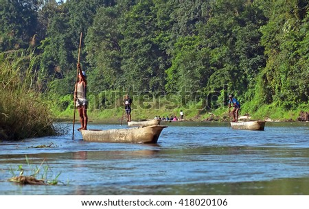 CHITWAN, NEPAL - OCTOBER 15, 2008: Local man traveling by rowboat at wild river in Chitwan National Park Nepal. Park was established in 1973 and granted the status of a World Heritage Site in 1984