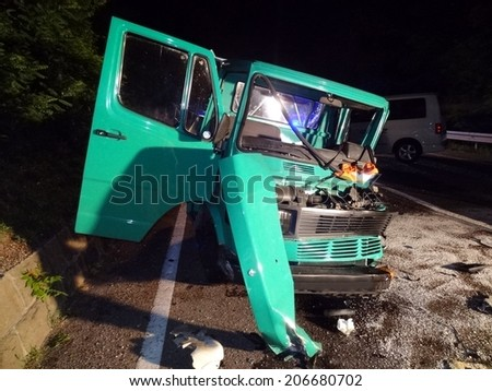 CHIUSA KLAUSEN, ITALY - JULY 12, 2013: frontal collision between taxi and truck on the road in the night. Car crash accident with injured taxi driver and motorist in Chiusa Klausen on July 12, 2013. - stock photo