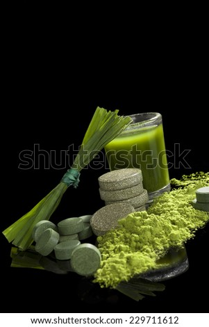 Chlorella, spirulina, wheat grass and young barley isolated on black background. Green superfood, healthy eating, alternative medicine and detox.  - stock photo