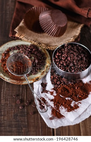 Choc Chips and Cocoa powder over dark wooden background. Selective focus, shallow DoF - stock photo