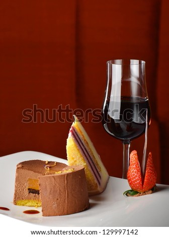 Chocolate and berries cake with glass of dessert wine - stock photo