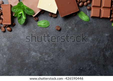 Chocolate and coffee beans on dark stone table. Top view with copy space - stock photo