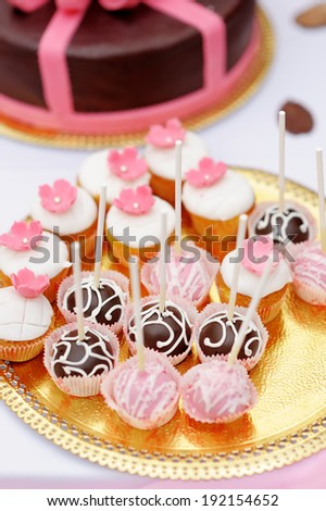 Chocolate and creamy pop cakes and cupcakes on golden plate - stock photo