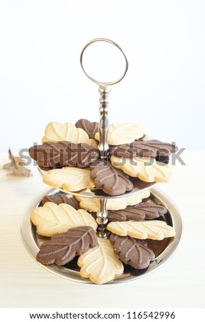 chocolate and lemon cookies in the form of oak leaves on a metal dessert shelves, wooden table in the background of autumn leaves - stock photo