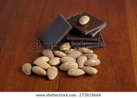 Chocolate and nuts on glossy wooden background - stock photo