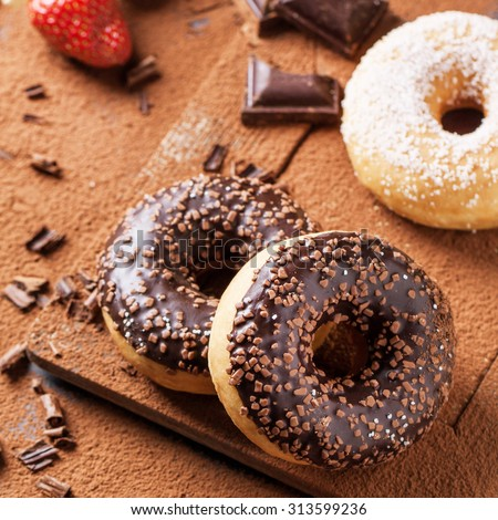 Chocolate and sugar donuts with fresh strawberries and dark chocolate served on cutting board with cocoa powder as background. Square image with selective focus - stock photo