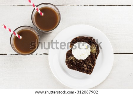Chocolate and vanilla cake with ice cream and cocoa drink on a white wooden background. Top view