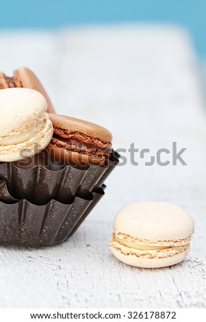 Chocolate and vanilla macarons over a rustic wooden background with copy space. Shallow depth of field with selective focus on vanilla macaron on table. - stock photo