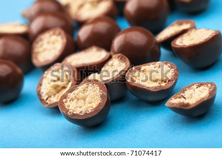 Chocolate balls and halves with crisp filling on blue background - stock photo