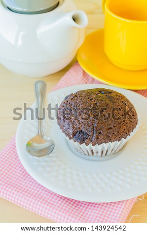 Chocolate banana cupcake on white dish with teapot&yellow tea cup