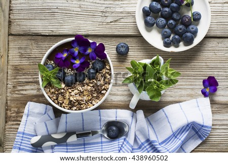 Chocolate Banana Smoothies Bowl with a topping of granola, blueberries, white sesame decorated with flowers purple garden viola on a simple wooden background. The concept of healthy organic breakfast - stock photo
