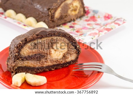 Chocolate banana strudel with a slice on a red plate