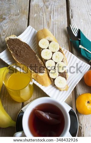chocolate banana  toast, chocolate spread with bread, tea, orange juice, fruit. healthy food, tasty concept - stock photo