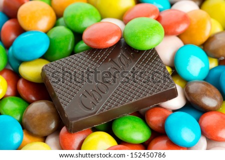 Chocolate bar and colorful candies - stock photo