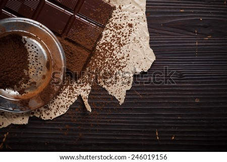 Chocolate bar with cacao powder on rustic brown wooden table - stock photo