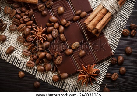 Chocolate bar with coffee beans, cinnamon and star anise on wooden table, rustic style - stock photo
