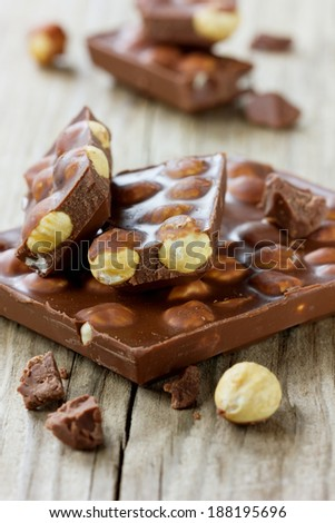 Chocolate bar with nuts on a wooden surface, selective focus - stock photo