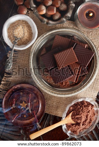 Chocolate bars and ingredients on a wooden table seen directly from above - stock photo