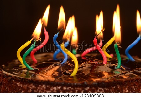 Chocolate birthday cake with candles lit.