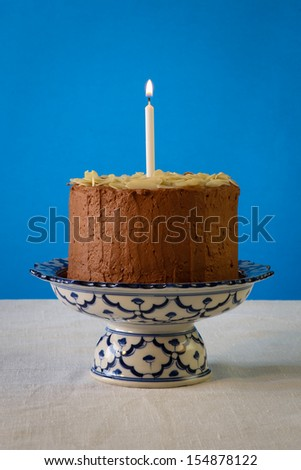Chocolate birthday party cake with almond flakes and burning candle on antique ceramic stand with blue pattern, blue background, white canvas - stock photo