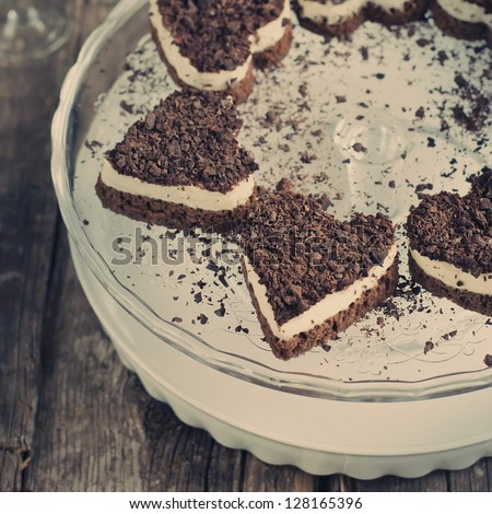 Chocolate Biscuit Valentine Cake in the Shape of Heart with White Custard and Crumb of Chocolate - stock photo