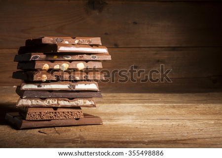 Chocolate blocks stack with different kind of chocolate on wooden background  - stock photo