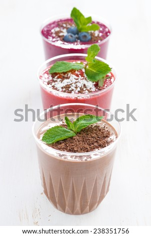 chocolate, blueberry and strawberry milkshakes in glasses, vertical, top view - stock photo