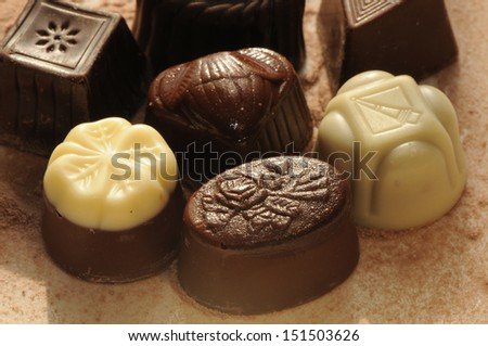 Chocolate bonbon, on a chocolate background. - stock photo