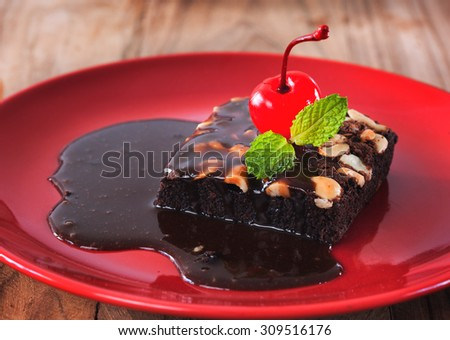 chocolate brownie with chocolate sauce and cherry - stock photo