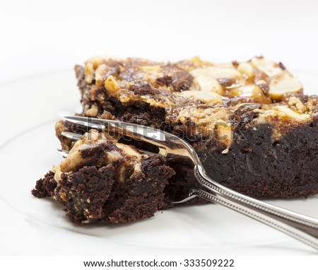 Chocolate brownie with honey and nut topping being cut with dessert fork