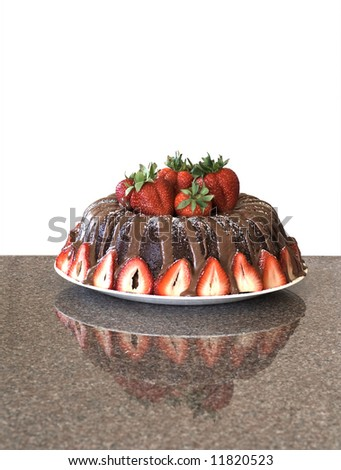 Chocolate bundt cake with fresh strawberries. Shot on granite with reflection. Background dropped out. - stock photo