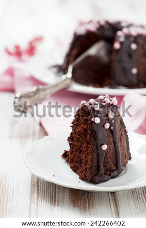 Chocolate bundt cake with pink decorations - stock photo
