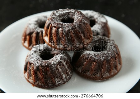 Chocolate bundt cakes on plate on black background - stock photo