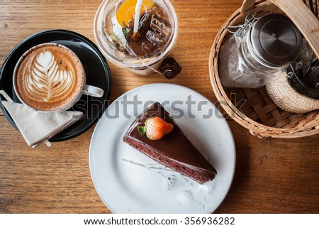 Chocolate cake, cappucino, peach tea and seasoning on a wood background - stock photo