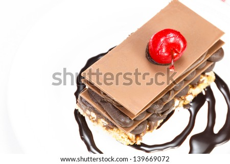 Chocolate cake. Chocolate cake with cherry on top on a white background - stock photo