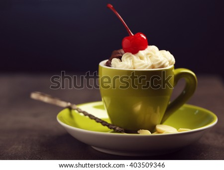 Chocolate cake in a green mug  with whipped cream and a cherry on top, close up - stock photo