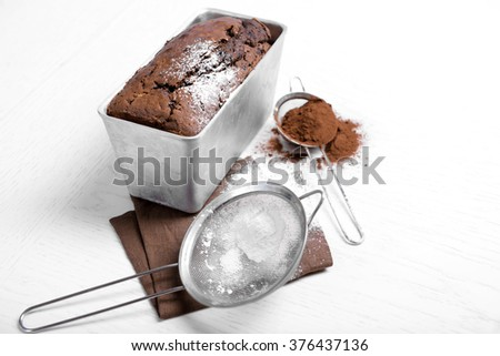 Chocolate cake in baking dish with powdered sugar on white table