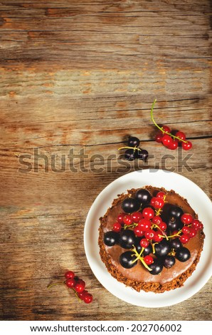 chocolate cake mini with red and black currants on a dark wood background. toning. selective focus on the currants on the cake - stock photo
